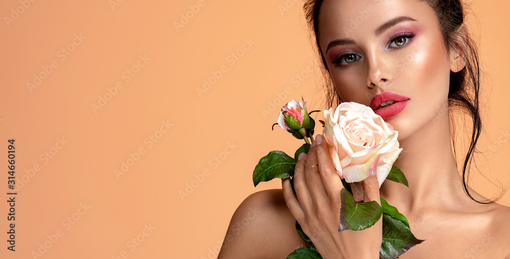 Fototapeta Beautiful white girl with rose.  Stunning brunette girl with white flower. Closeup face of young beautiful woman with a healthy clean skin. Pretty woman with bright makeup