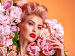 Leinwandbild Motiv Beautiful white girl with flowers. Stunning blonde girl with big bouquet flowers of roses. Closeup face of young beautiful woman with a healthy clean skin. Pretty woman with bright makeup