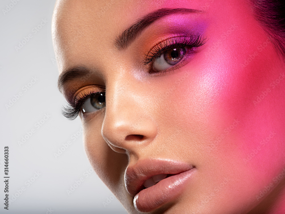 Fototapeta Beautiful white girl with bright eye-makeup. Beautiful fashion woman with  a red  flare on face.   Glamour fashion model with bright gloss make-up posing at studio. Stylish fashionable concept. Art.