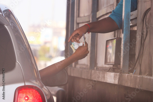 Obraz na plátně Indian Asian Person In Car Paying Money And Receiving Receipt From Toll Tax Coll