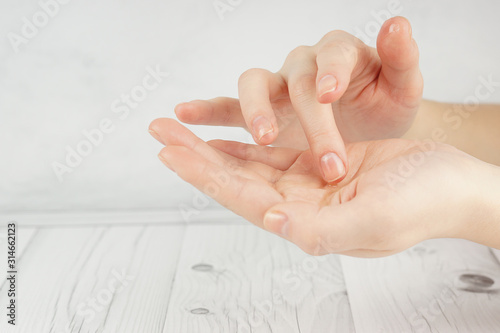 Foto Hands of a young girl with good skin, oil is poured in one hand, the finger take