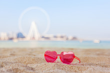 Pink Sunglasses On A Sandy Beach With Views Of The Dubai Eye Ferris Wheel, Honeymoon, Relaxation, Copy Space