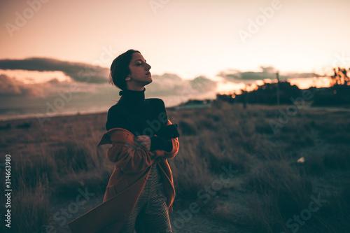 Fotografie, Tablou Ragazza strafottente guarda di lato sulla spiaggia al tramonto.