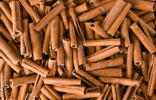 Fotografía Cinnamon background. Pile of cinnamons stick top view.