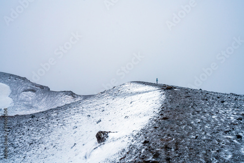 Girl with blue jacket stands on top of a volcano in geothermal and volcanic area near Krafla in Iceland Wallpaper Mural