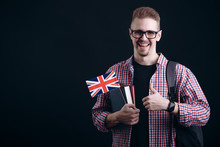 Young Male English Student With Flag And Books Showing Thumb Up Isolated Black Background