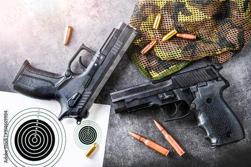 Fototapeta Hand guns with target on dark stone table top view