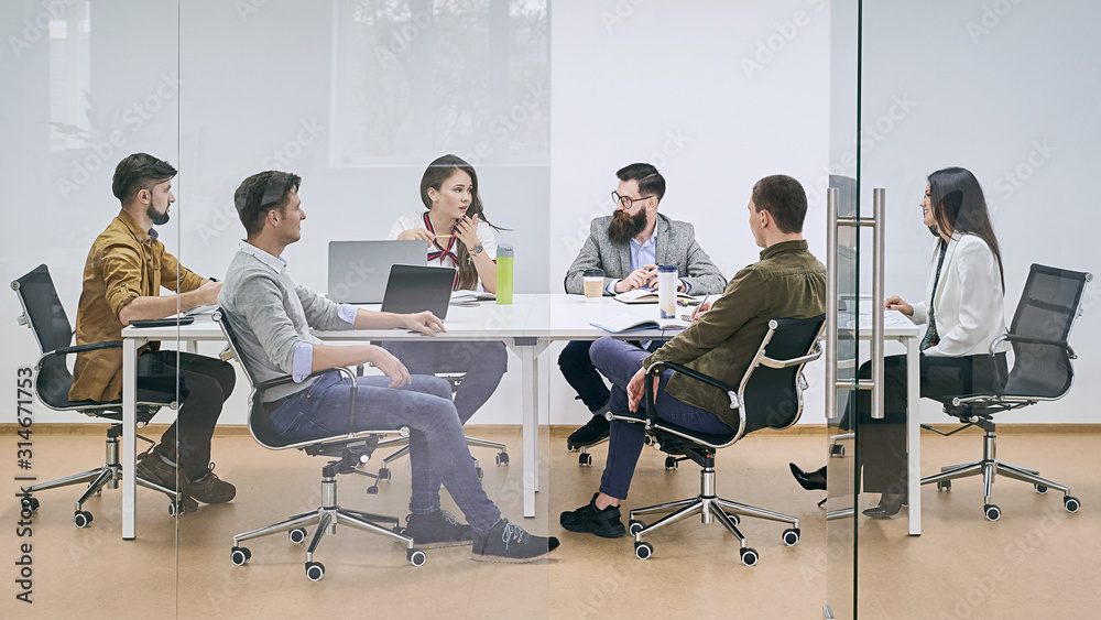 Fototapeta Corporate business team and manager in a meeting at IT company office conference room. View through glass wall.
