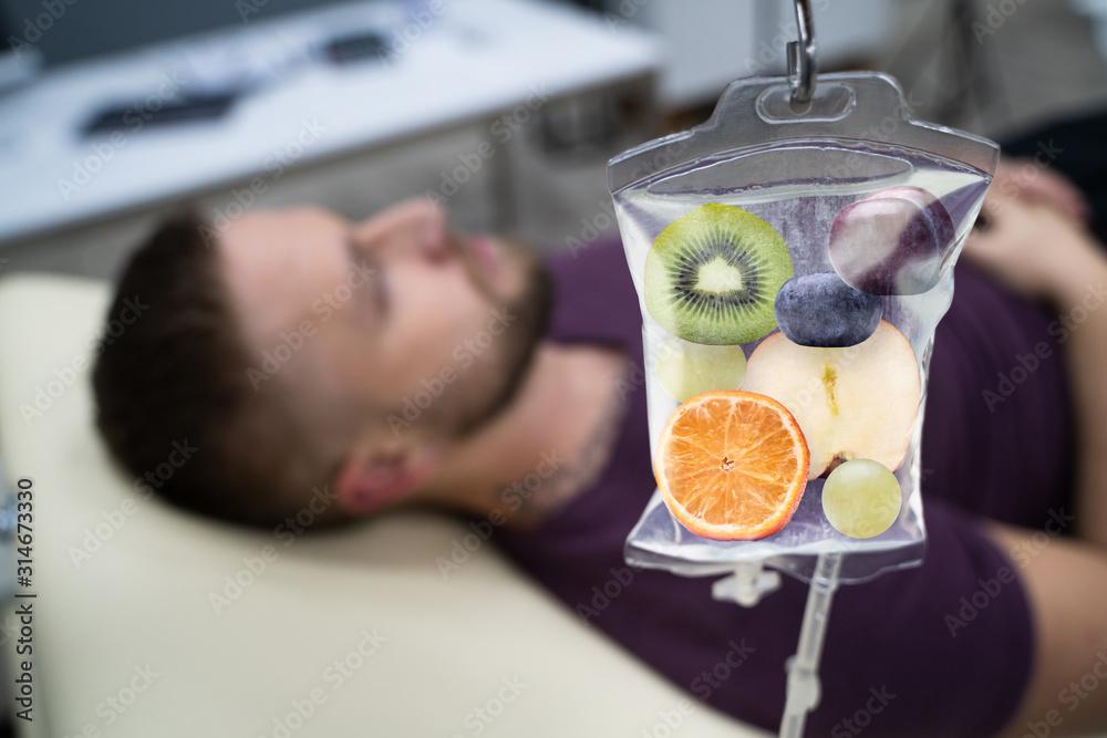 Fototapeta Fruit Slices Inside Saline Bag Hanging In Hospital