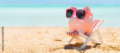 Foto Pink Piggybank On Deck Chair Over The Sandy Beach