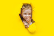 canvas print picture - A little funny red-haired girl picks her nose and squints her eyes in pleasure. Yellow background, torn paper, hole. The concept of bad behavior. Copy space.