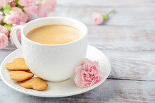 Cup Of Fresh Morning Coffee With Pink Carnation Flowers On A Wooden Background. Valentine's Day Concept.