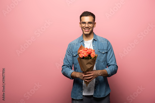 Obraz Handsome man smiling at camera while holding bouquet on pink background - fototapety do salonu