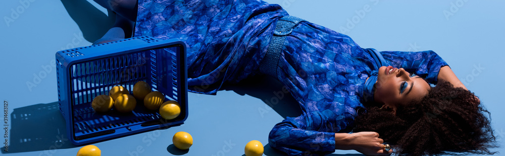 Fototapeta panoramic shot of african american woman lying with shopping basket and lemons on blue background