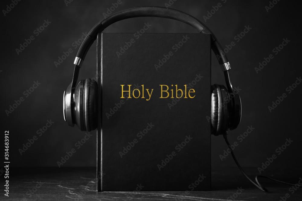 Fototapeta Bible and headphones on black background. Religious audiobook