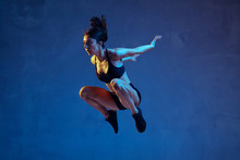 Caucasian Young Female Athlete Practicing On Blue Studio Background In Neon Light. Close Up Of Sportive Model Jumping High, Running. Body Building, Healthy Lifestyle, Beauty And Action Concept.
