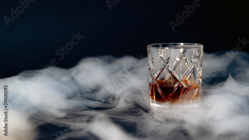 Glass of whiskey on a table covered with smoke against a black background
