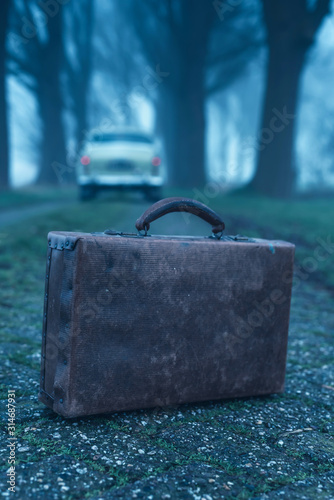 Old briefcase on country road during foggy dusk with classic car in the background.
