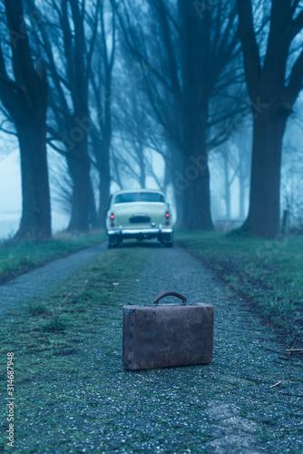 Stara teczka na wiejskiej drodze podczas mgłowego półmroku z klasycznym samochodem w tle.