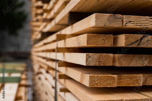 Fototapeta Piles of wooden boards in the sawmill, planking. Warehouse for sawing boards on a sawmill outdoors. Wood timber stack of wooden blanks construction material. Industry. obraz