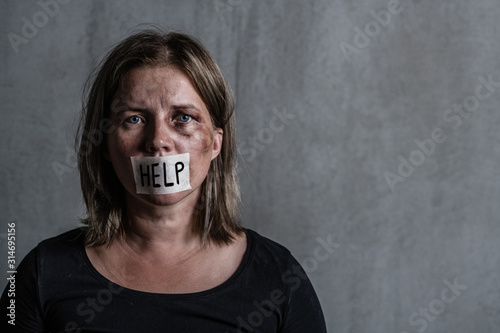 Fototapeta Beaten up woman victim of domestic violence and abusewith covered her mouth taped with the inscription help