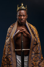 African Man In A Crown And Cloak Holds A Sword In His Hand.
