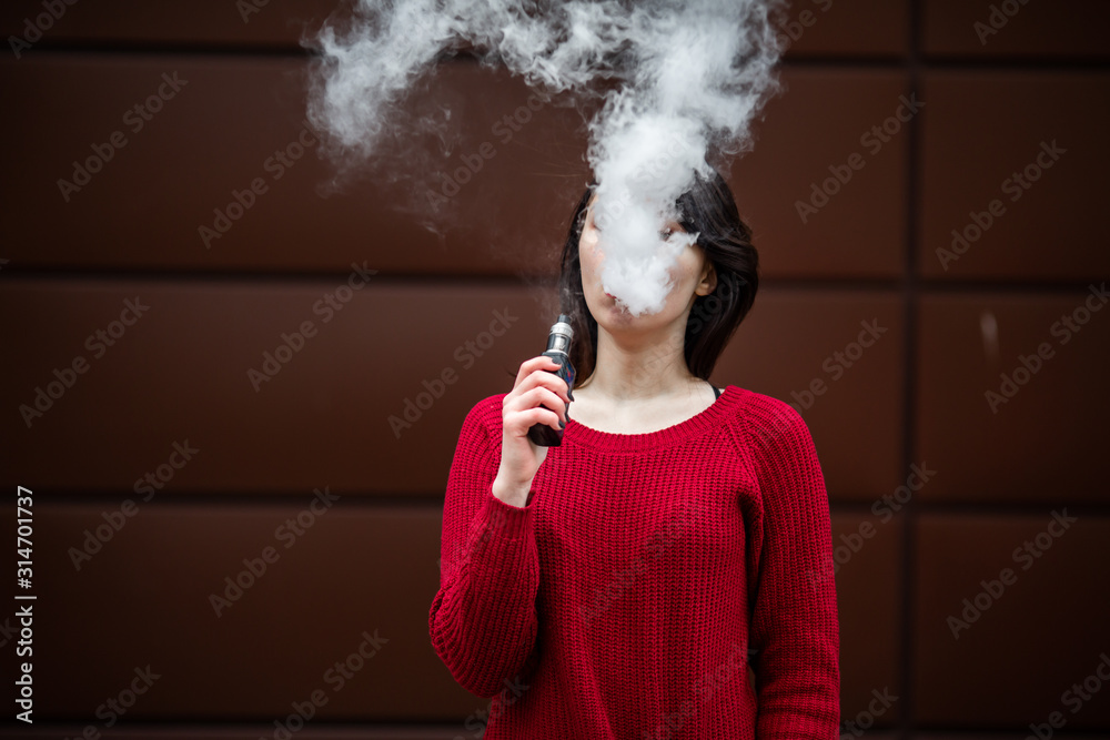 Fototapeta Vape teenager. Young pretty white caucasian girl in a red sweater smoking an electronic cigarette opposite modern brown background on the street in the winter. Deadly bad habit.