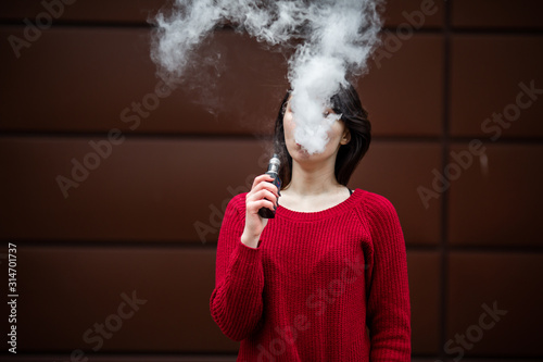 Obraz Vape teenager. Young pretty white caucasian girl in a red sweater smoking an electronic cigarette opposite modern brown background on the street in the winter. Deadly bad habit. - fototapety do salonu