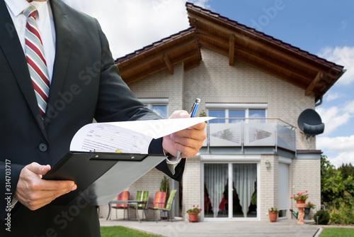 Man Checking Documents Standing Near House Wallpaper Mural