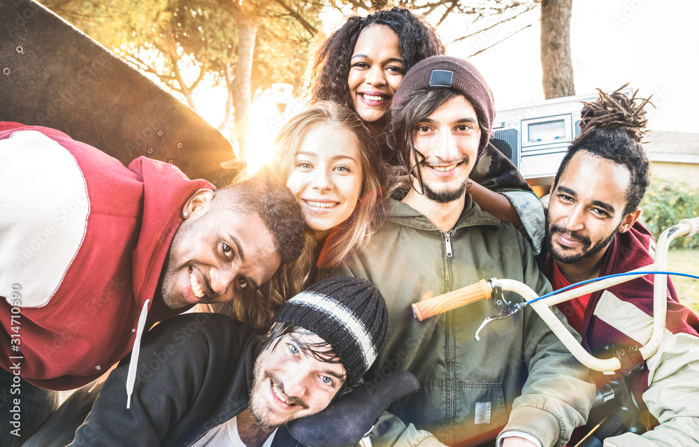 Fototapeta Multiracial best friends taking selfie at bmx skate park contest - Happy youth and friendship concept with young millenial people having fun together in urban city area - Bright warm sunshine filter