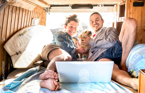 Fotografie, Tablou Digital nomad couple with cute dog using laptop on retro mini van transport - Tr