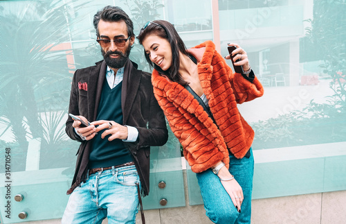Leinwand Poster Modern hipster couple having fun using mobile smart phone outside - Social inter