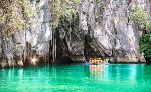 Obraz Cave entrance of Puerto Princesa subterranean underground river with longtail boat - Wanderlust travel concept at Palawan exclusive Philippine destination - Vivid filter with bulb torch light sunflare - fototapety do salonu
