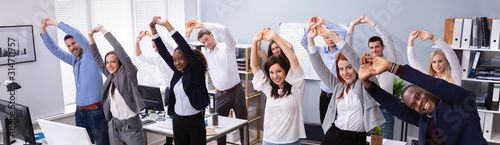 Leinwand Poster Young Businesspeople Doing Stretching Exercise At Workplace