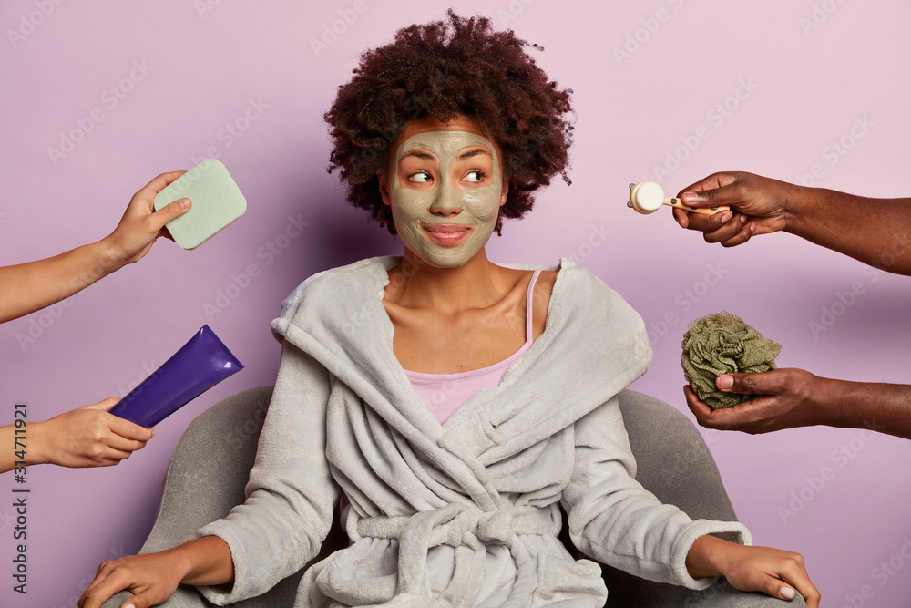 Fototapeta Relaxed curly haired woman wears clay mask on face, cares about facial skin, gets various cosmetic treatments after taking bath, looks aside, sits in comfortable armchair, wears domestic clothes