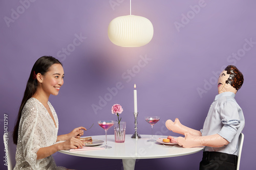 Horizontal shot of happy Korean woman enjoys time with unreal imaginary man, dreams about perfect relationships, has fake love, waits for boyfriend at festive dinner table with male doll Wallpaper Mural