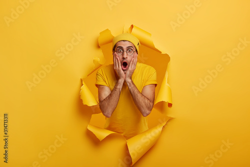 Fototapeta Speecheless impressed guy keeps hands on cheeks, stares at camera with opened mouth, gossips about something, wears yellow casual clothes, stands in ripped hole background. Emotions concept. obraz na płótnie