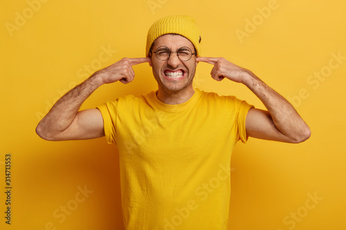 Photo Half length shot of annoyed guy clenches teeth, plugs ears with index fingers, ignores annoying sound, feels ear pain or ache, bothered by bad loud unpleasant noise, wears yellow clothes