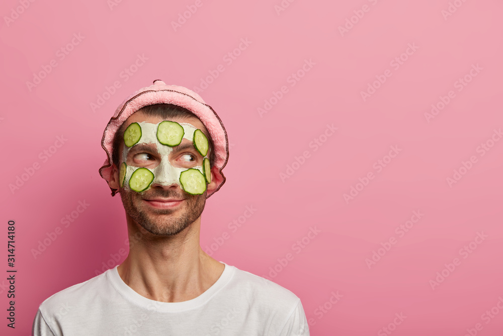 Fototapeta Good tempered happy man wears face mask and cucumbers, enjoys morning spa procedure, wants to look refreshed, stands in white t shirt against pink background, copy space. Skin care, grooming