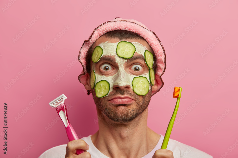 Fototapeta Dermatology, wellness and grooming concept. Headshot of emotional man applies facial cosmetic scrub with cucumber slices, poses with razor and toothbrush, has beauty treatments at morning time