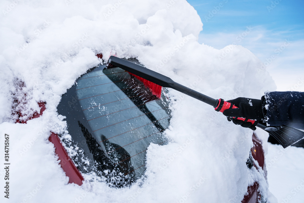 Fototapeta Woman Cleaning Car From Snow
