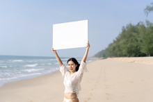 Woman In Bikinis Holding Blank White Board On The Beach.