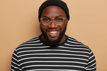 Close Up Portrait Of Dark Skinned Adult Man With Thick Bristle, Smiles Toothy, Wears Big Optical Glasses, Striped Jumper, Glad To Meet Friend, Isolated Over Beige Studio Background, Has Good Day
