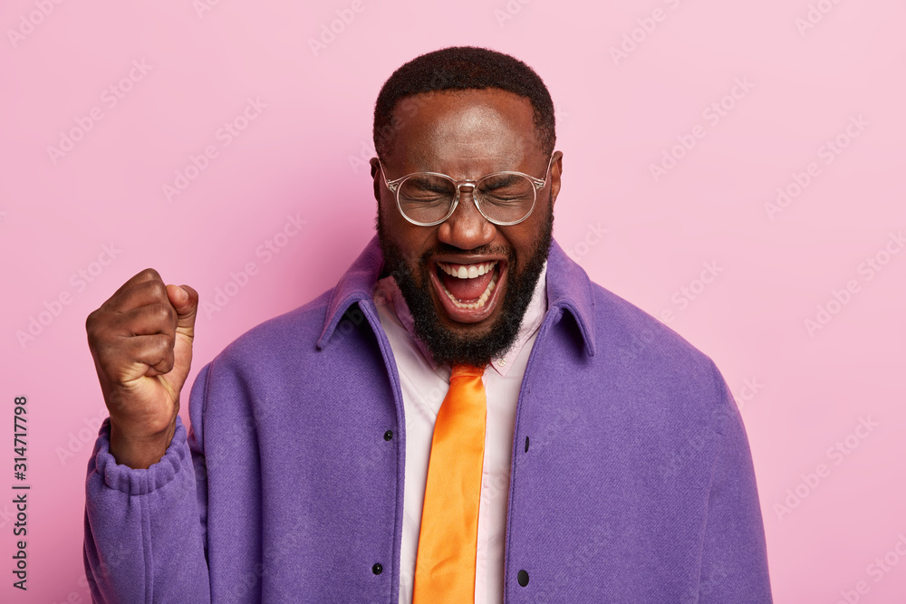 Fototapeta Pleased dark skinned man raises clenched fist, shouts yeah, celebrates success, wears orange tie, purple jacket, stands against pastel background, celebrates triumph, gets promotion in company