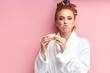 attractive satisfied girl eating sweet tasty donut after shower, dressed in white bathrobe, curlers on hair. Isolated pink background