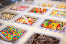 A View Of Several Containers Full Of Popular Ice Cream Toppings On Display At A Local Ice Cream Shop.