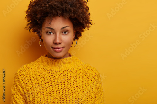 Obraz Portrait of Afro American millennial woman with calm serious face expression, looks directly at camera, wears knitted jumper, has natural beauty, models against yellow studio wall with empty space - fototapety do salonu