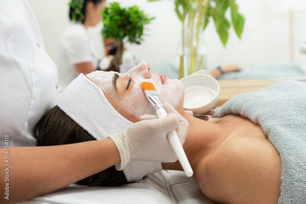 Fototapeta Dermatolog wykonuje zabieg leczniczy na twarzy kobiety. Maska w salonie kosmetycznym. Kosmetyczka trzyma w dłoni pędzel i nakłada kosmetyk na twarz kobiety.