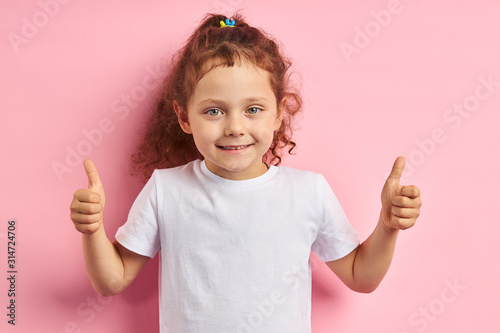 Obraz Smiling girl 5 years old thumbs up, looking at camera. Wearing white t-shirt, stand isolated over pink background - fototapety do salonu