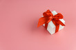 canvas print picture - white gift box with red strap on colour background, engagement ring box